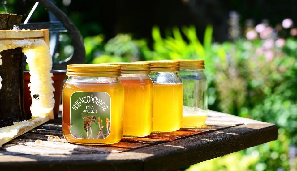 ετικέτα μελιού σε βάζα με μέλι δίπλα από κερήθρες