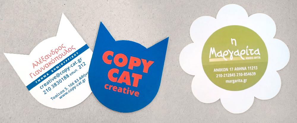αριστερά οι δύο όψεις μιας επαγγελματικής κάρτας σε σχήμα γάτας και δεξιά σε σχήμα μαργαρίτας