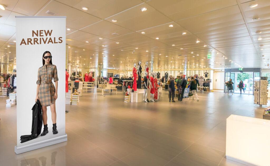 μαγαζί με ρούχα στο εσωτερικό του οποίου έχει αναρτηθεί rollup banner για να δείξει τα καινούργια του προϊόντα